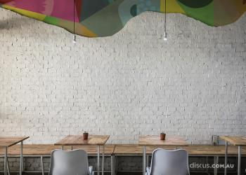 Felici Carnaval as textured wall graphic crushed stone. This electric graphic delivers a colour pop and contrast to the feature wall of this industrial-style cafe.