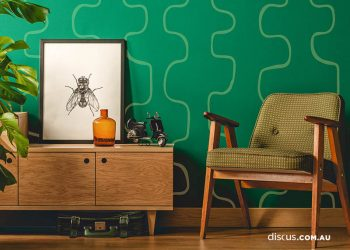 Simple vintage room interior with green walls, wooden floor, green chair, cupboard, poster and plant